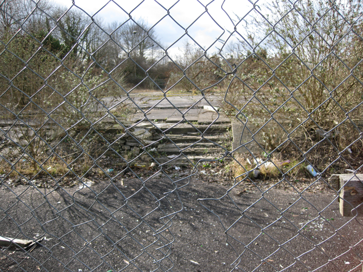 a chain link fence with a hole looking into a scrubland and concrete area