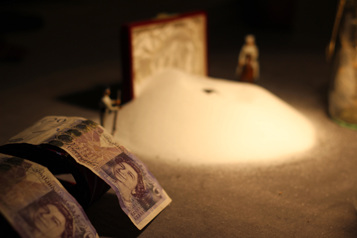 Two 20 pound notes beside a pile of table salt with two model soldiers guarding it, on the Common Salt table