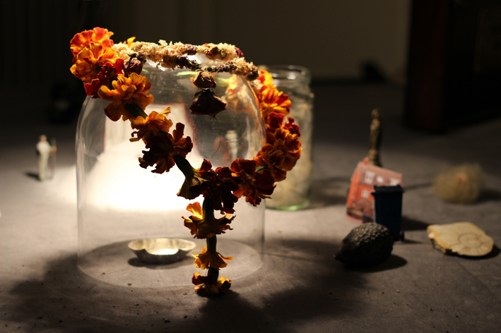 Marigold flower garland hangs over a glass dome with a salt cellar inside