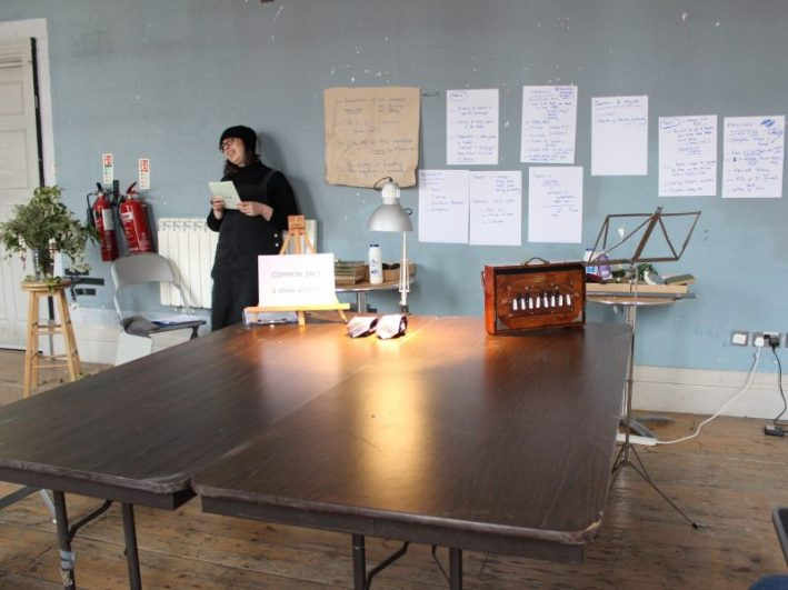 Sheila leans against the wall behind the table while rehearsing Common Salt at Battersea Arts Centre